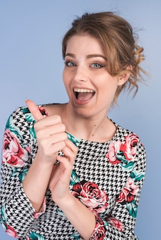 Mujer feliz atractiva en vestido con el pulgar para arriba