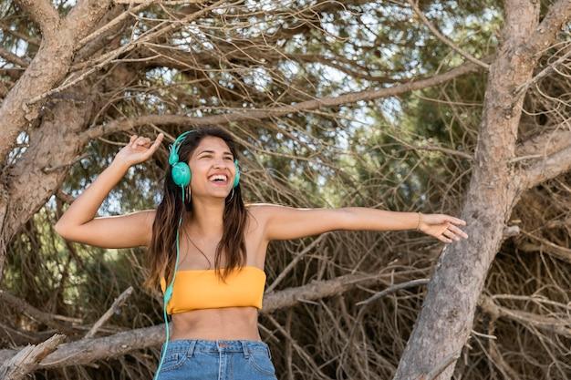 Mujer feliz en auriculares escuchando música en el bosque