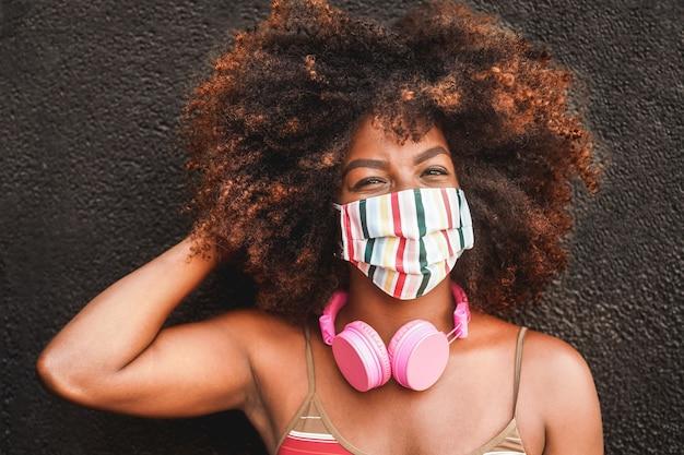 Mujer feliz con auriculares con mascarilla durante el brote de coronavirus