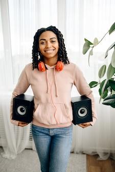 Mujer feliz en auriculares tiene dos altavoces de audio y escucha música. señora bonita relajarse en la habitación, amante del sonido femenino descansando
