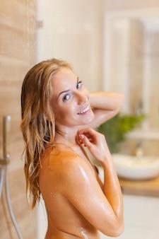 Mujer feliz bañándose bajo la ducha