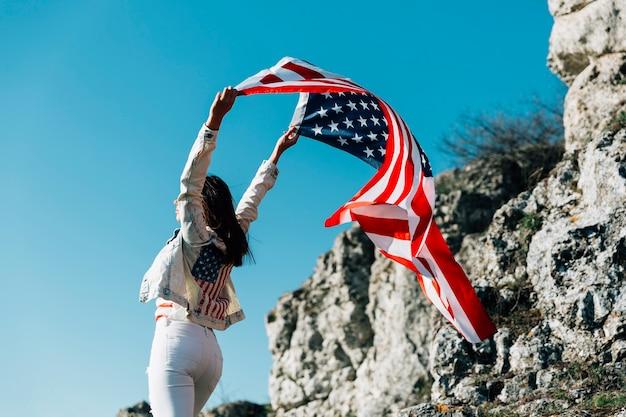 Mujer feliz con la bandera americana que vuela