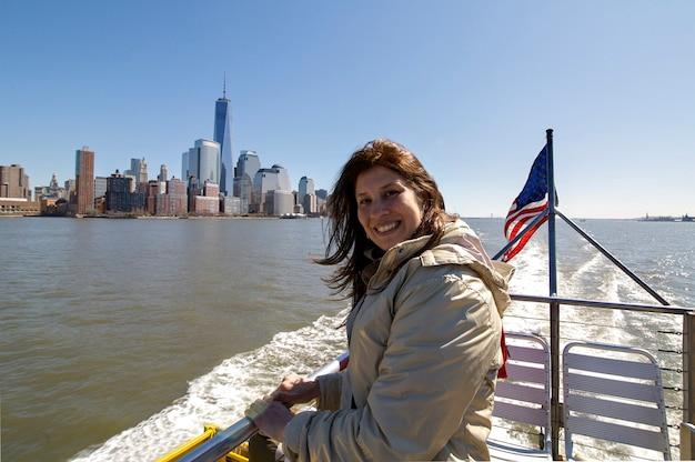 Mujer feliz en barco con manhattan y la bandera de estados unidos