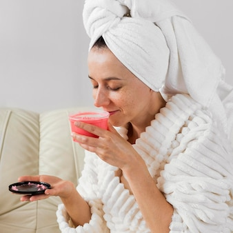 Mujer feliz en bata de baño que huele una crema