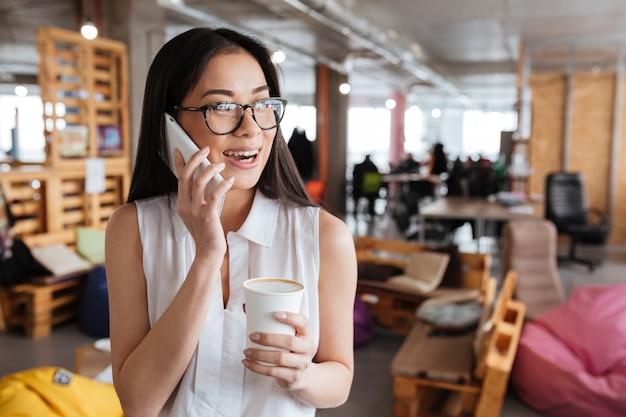 Mujer feliz bebiendo café lattee y hablando por teléfono móvil