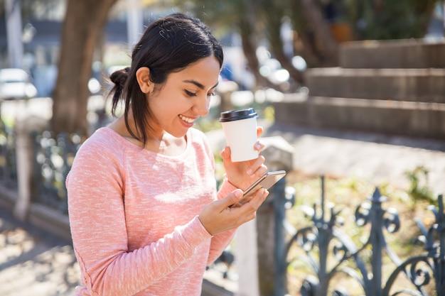 Mujer feliz bebiendo café y navegando en smartphone al aire libre