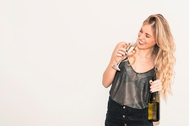Mujer feliz bebiendo champán de vidrio