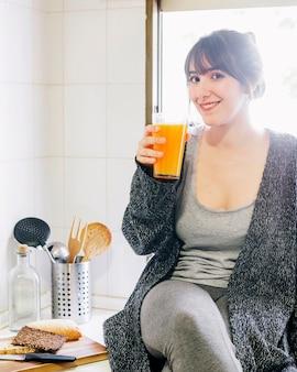 Mujer feliz bebiendo jugo en la cocina