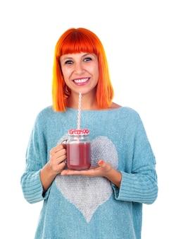 Mujer feliz bebiendo un jugo de desintoxicación rosa