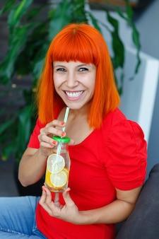 Mujer feliz bebiendo una limonada en casa