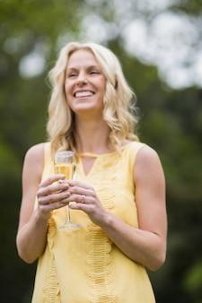 Mujer feliz bebiendo vaso de champán afuera