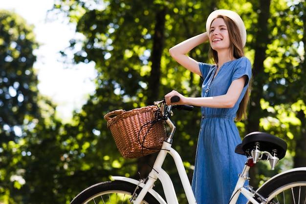 Mujer feliz con bicicleta mirando a otro lado