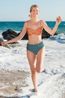 Mujer feliz en bikini en la playa en su retrato de cuerpo entero de vacaciones