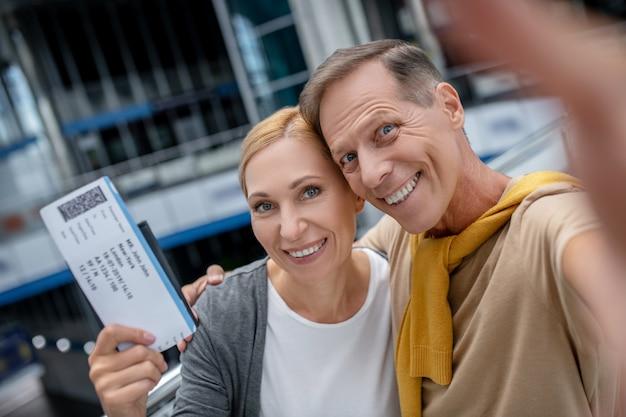 Mujer feliz con boleto y hombre abrazando Foto Premium