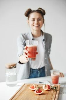 Mujer feliz con los bollos que sonríen estirando el batido de desintoxicación del pomelo sobre la pared blanca. comida de dieta saludable. se centran en el vidrio.