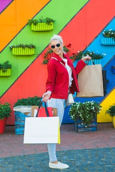 Mujer feliz con bolsas cerca de pared de colores