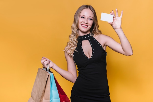 Mujer feliz con bolsas de compra y tarjeta