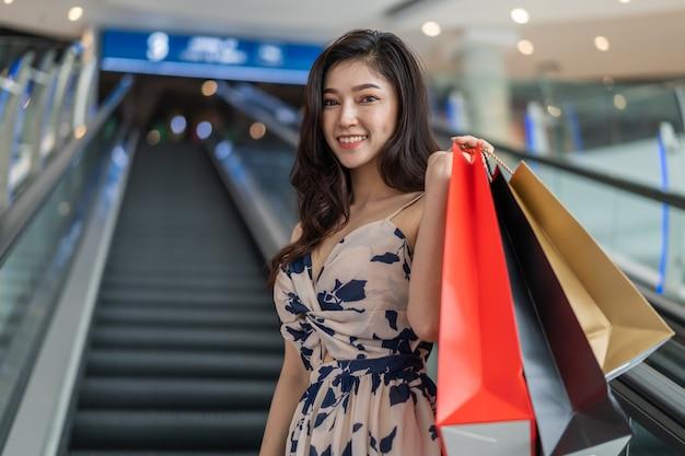 Mujer feliz con bolsas de compras en la escalera mecánica en el centro comercial