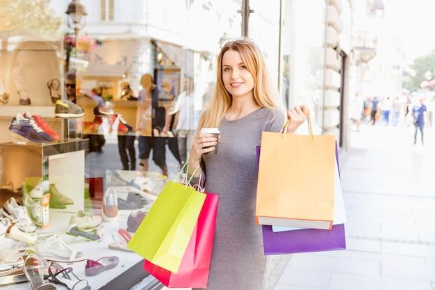 Mujer feliz con bolsas de compras multicolores junto a la vitrina de una tienda