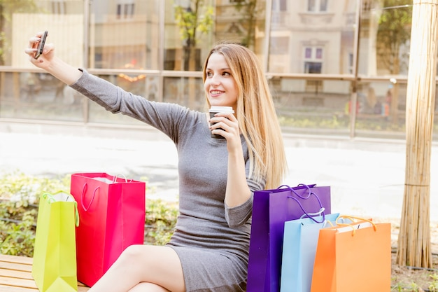 Mujer feliz con bolsas de compras multicolores tomando selfie en teléfono móvil