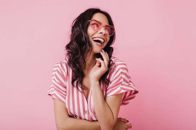 Mujer feliz con cabello castaño ondulado riendo. chica jocund en traje rosa a rayas sonriendo.