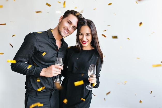 Mujer feliz con cabello lacio oscuro celebrando el aniversario con su marido