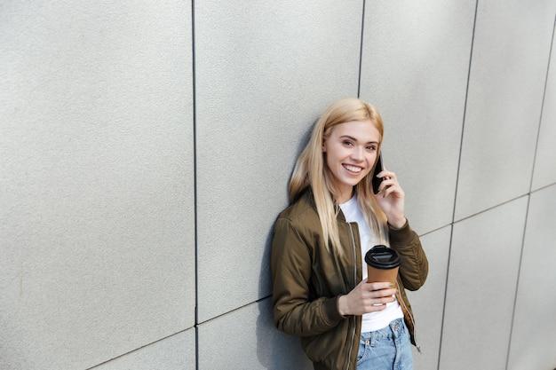 Mujer feliz con café hablando por teléfono inteligente