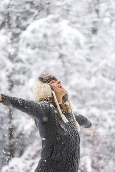 Mujer feliz en la caída de nieve con los brazos abiertos