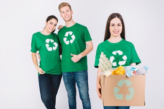 Mujer feliz con caja de cartón llena de artículos de reciclaje