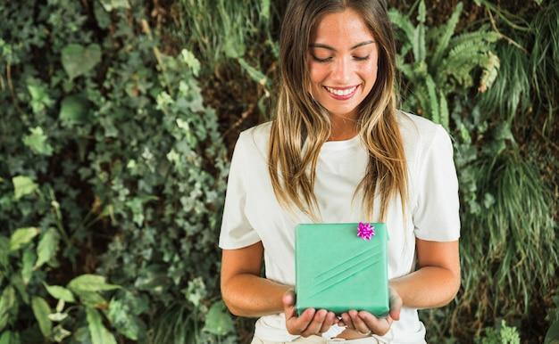 Mujer feliz con caja de regalo verde en frente de fondo de hojas verdes