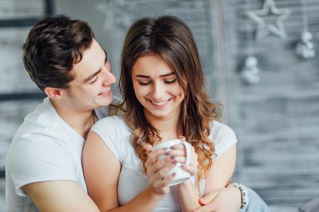 Mujer feliz en la cama con su hombre, sostiene una taza de té y disfruta del tiempo juntos