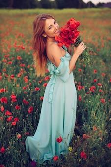 Mujer feliz caminando por el campo de amapolas en flor