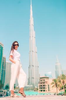 Mujer feliz caminando en dubai con rascacielos en el fondo.