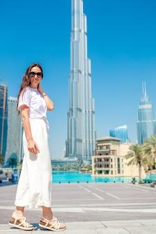 Mujer feliz caminando en dubai con rascacielos