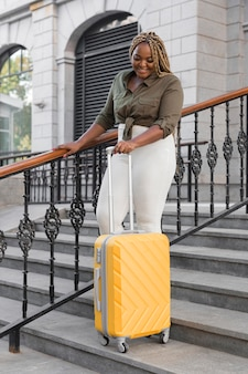 Mujer feliz caminando por las escaleras con un equipaje