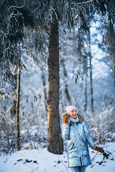 Mujer feliz caminando en un parque de invierno