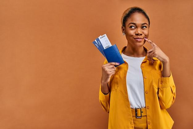 Mujer feliz en camisa amarilla sonríe con un pasaporte con entradas pensativamente mira hacia otro lado. concepto de viaje