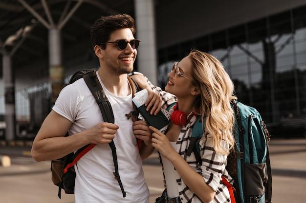 Mujer feliz en camisa a cuadros y hombre en camiseta blanca sonríe cerca del aeropuerto