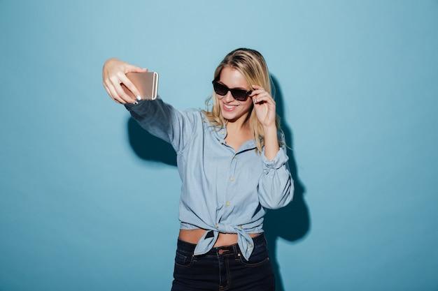 Mujer feliz en camisa y gafas de sol haciendo selfie en smartphone