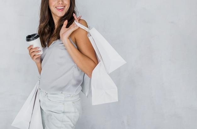 Mujer feliz en camiseta con redes de compras y café