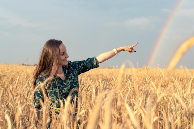 Mujer feliz en campo de trigo con espiguillas doradas apuntando su dedo al arco iris
