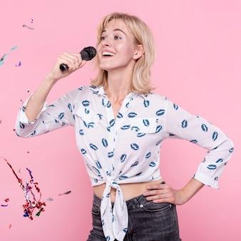 Mujer feliz cantando karaoke en fiesta