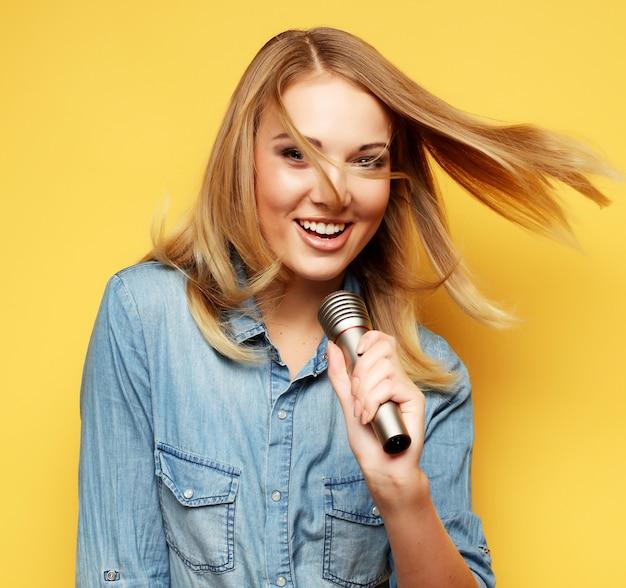 Mujer feliz cantando en el micrófono sobre fondo amarillo