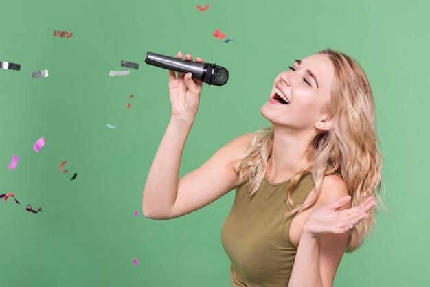 Mujer feliz cantando rodeada de confeti