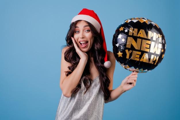 Mujer feliz celebración feliz año nuevo globo y sombrero de santa