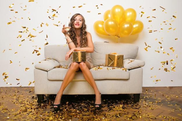 Mujer feliz celebrando el año nuevo en confeti dorado sentado en el sofá