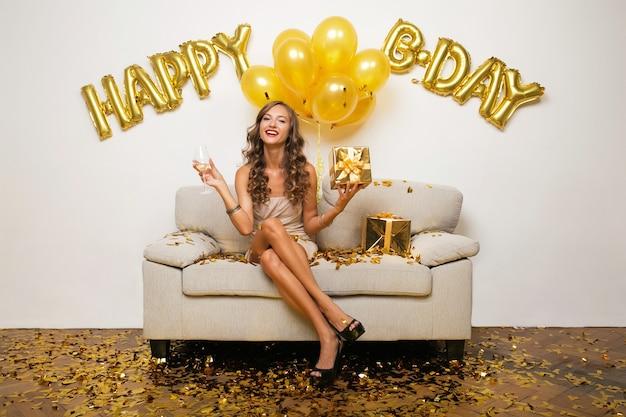 Mujer feliz celebrando un cumpleaños en confeti dorado sentado en el sofá