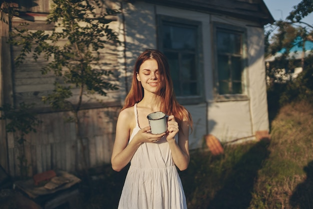 Mujer feliz cerca del edificio con taza de hierro al aire libre en el jardín.
