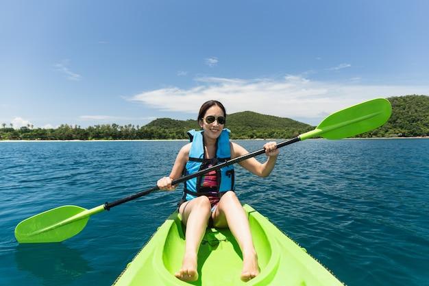 Mujer feliz con chaleco salvavidas en kayak en el océano de la isla tropical de vacaciones.