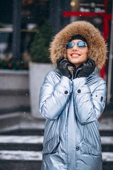 Mujer feliz en chaqueta azul de pie junto a la cafetería